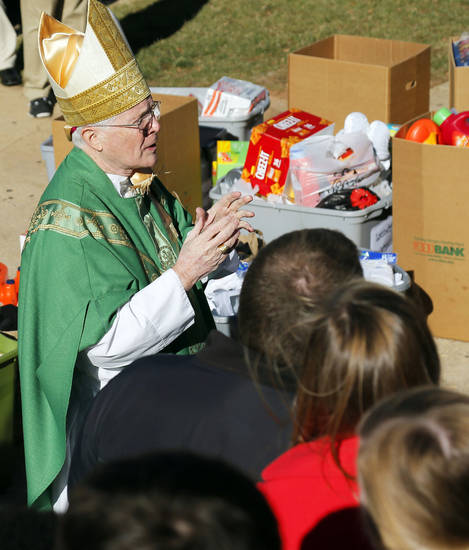 Bishop Edward J. Slattery, of Tulsa, speaks to gathered basketball players after they brought donated items Friday to Sacred Heart Catholic Church, 2706 S Shartel, in Oklahoma City. Players from the Catholic boys and girls teams participating in the Hoops 4 Hope tournament loaded items they donated to Catholic Charities into a truck after having Mass to start the event. Photo by Nate Billings, The Oklahoman <strong>NATE BILLINGS</strong>