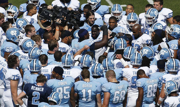 North Carolina's Travis Bond (76) high-fives with the team prior to an NCAA college football spring scrimmage game in Chapel Hill, N.C., Saturday, April 14, 2012. (AP Photo/Gerry Broome)