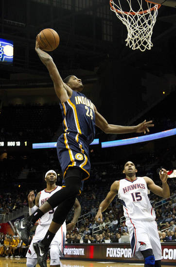 Indiana Pacers small forward Paul George (24) scores as Atlanta Hawks' Josh Smith (5) and Al Horford (15) look on in the first half of an NBA basketball game on Wednesday, Nov. 7, 2012, in Atlanta. (AP Photo/John Bazemore)