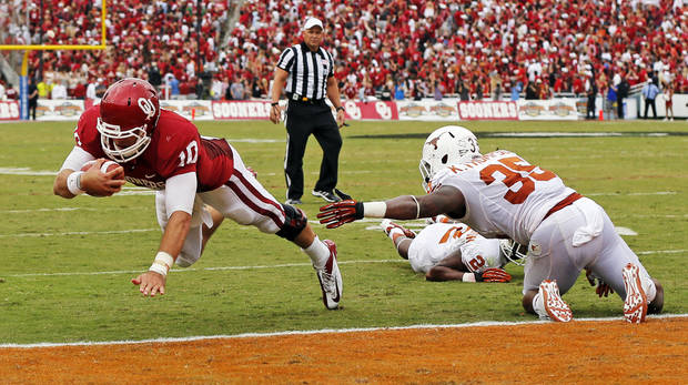 OU's Blake Bell (10) dives for a touchdown past UT's Kendall Thompson (35) in the second quarter during the Red River Rivalry college football game between the University of Oklahoma (OU) and the University of Texas (UT) at the Cotton Bowl in Dallas, Saturday, Oct. 13, 2012. Photo by Nate Billings, The Oklahoman