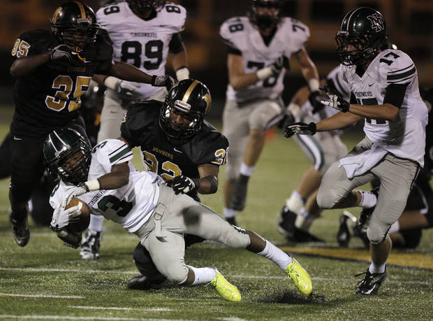 Norman North's Bryan Payne (3) is taken down by Midwest City's Meli Brewer (22)  during a high school football game between Midwest City and Norman North in Midwest City, Friday, Sept. 21, 2012.  Photo by Garett Fisbeck, The Oklahoman