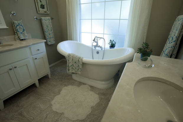 The Greenhaws' master bathroom features separate vanities and a luxurious tub. PHOTO BY STEVE SISNEY, THE OKLAHOMAN <strong>STEVE SISNEY</strong>