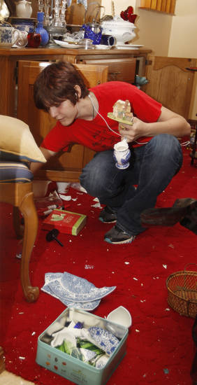 Mercedes Osolin reaches under a chair to retrieve a non-broken item at her grandparents' home in Sparks, Okla., Sunday, Nov. 6, 2011. The home was damaged when an earthquake struck the area. (AP Photo/Sue Ogrocki) ORG XMIT: OKSO105