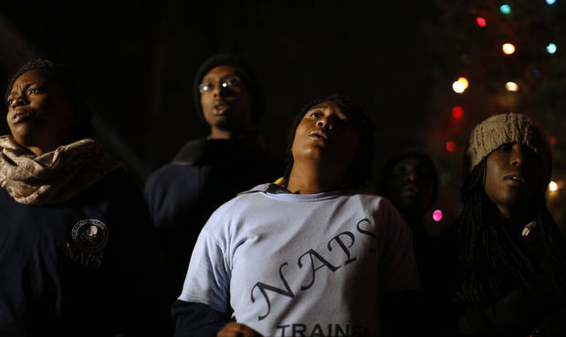 Members of the National Association for the Prevention of Starvation choir sing at a memorial to shooting victims, Monday, Dec. 17, 2012, in Newtown, Conn. A gunman walked into Sandy Hook Elementary School in Newtown Friday and opened fire, killing 26 people, including 20 children. (AP Photo/Jason DeCrow) ORG XMIT: CTJD122