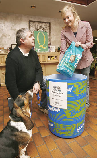 As she donates pet food, Abbey Fint talks to Gary Pierce, a pet food bank volunteer and donor, and his basset hound, Joe, who was rescued by Pierce two years ago. Animal advocates have begun a pet food bank and are seeking food donations to aid pet owners needing help feeding their animals during difficult economic times. Photo by Jim Beckel, The Oklahoman