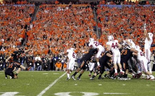 Oklahoma State kicker Quinn Sharp (13) kicks the game-winning field goal as teammate Wes Harlan (11) holds against Stanford during overtime of the Fiesta Bowl NCAA college football game, Monday, Jan. 2, 2012, in Glendale, Ariz. Oklahoma State won 41-38. (AP Photo/Matt York)