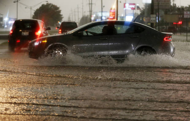 Cars drive through water at NW 39th and Meridian during heavy rain in Oklahoma City, Friday, May 31, 2013. Severe thunderstorms brought tornadoes, high winds, heavy rain and hail to central Oklahoma on Friday. Photo by Nate Billings, The Oklahoman
