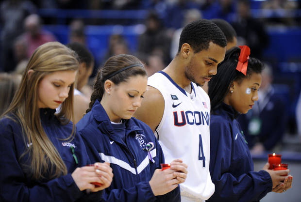 Members of the Connecticut's cheer, dance and basketball teams participate in a service honoring those killed in a school shooting in Newtown, Conn., last Friday. The service was held before an NCAA college basketball game between Connecticut and Maryland Eastern Shore in Hartford, Conn., Monday, Dec. 17, 2012. (AP Photo/Fred Beckham) ORG XMIT: CTFB102