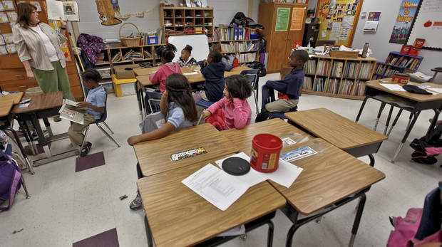 Desks sit empty in the first grade class of Michelle Kenery as students listen to her read a story at North Highland Elementary on Tuesday, Jan. 15, 2013, in Oklahoma City, Okla. The school has been one of the most effected in the metro by the arrival of flu season.   Photo by Chris Landsberger, The Oklahoman