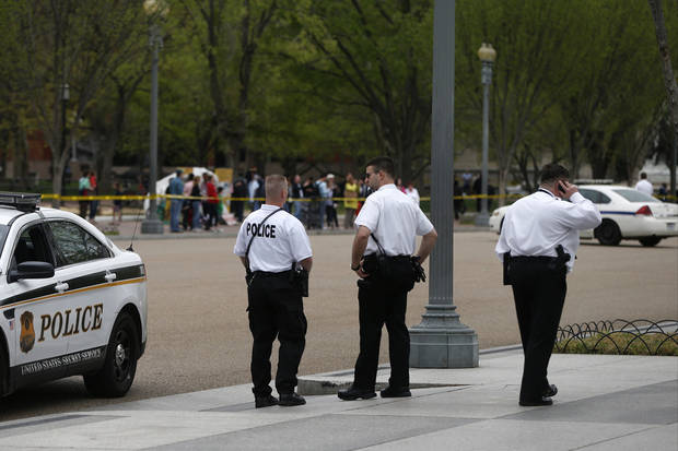 Uniformed Division Secret Service officers stand watch on the sidewalk in front of the White House looking north from Pennsylvania Avenue during heightened security following the explosions in Boston, Monday, April 15, 2013 in Washington. (AP Photo/Charles Dharapak) ORG XMIT: WHCD101