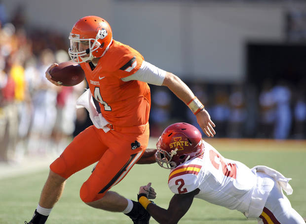 Oklahoma State quarterback J.W. Walsh, left, escapes from Iowa State defensive back, Jansen Watson, right, during the first half of an NCAA college football game in Stillwater, Okla. Saturday, Oct. 20, 2012. Walsh accounted for 46 yards rushing and one of the Oklahoma State touchdowns in the 31-10 win over Iowa State. (AP Photo/Brody Schmidt) ORG XMIT: OKBS105