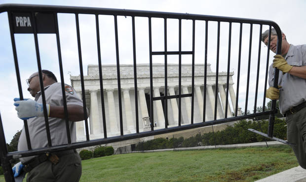 National Park Service employees remove barricades from the grounds of the Lincoln Memorial in Washington, Thursday, Oct. 17, 2013. Barriers went down at National Park Service sites and thousands of furloughed federal workers began returning to work throughout the country Thursday after 16 days off the job because of the partial government shutdown.(AP Photo/Susan Walsh)