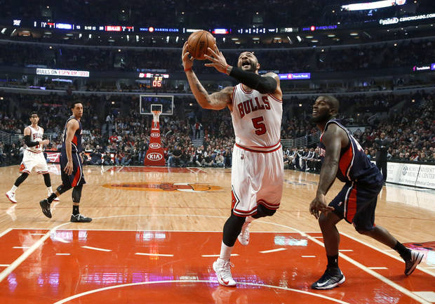 Chicago Bulls forward Carlos Boozer (5) shoots past Atlanta Hawks forward Ivan Johnson during the first half of an NBA basketball game Monday, Jan. 14, 2013, in Chicago. (AP Photo/Charles Rex Arbogast)