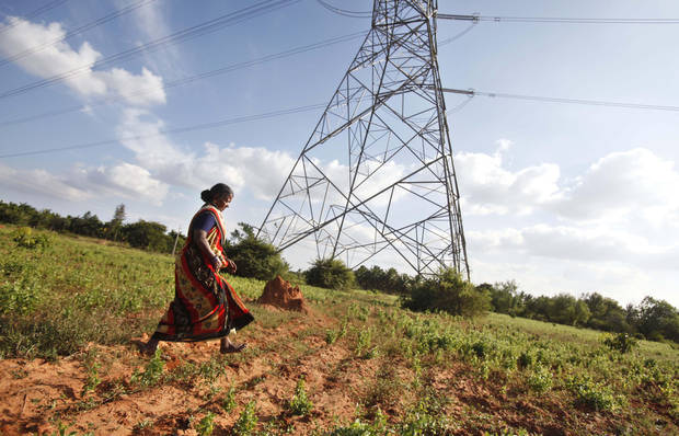 In this Dec. 5, 2012 photo, Gangarangamma, 65, walks through the land she and her husband farmed for decades which the records show is registered to the government, a sign the land remained in dispute, in village Karadigere Kaval, 85 kilometers (53 miles) from Bangalore, India. For years, Karnataka's land records were a quagmire of disputed, forged documents maintained by thousands of tyrannical bureaucrats who demanded bribes to do their jobs. In 2002, there were hopes that this was about to change. (AP Photo/Aijaz Rahi)