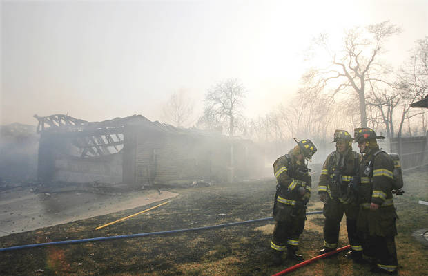 Spencer firefighters rest Thursday after extinguishing flames at a house in the Oakwood East Addition in Midwest City. Photo by JIM BECKEL, THE OKLAHOMAN