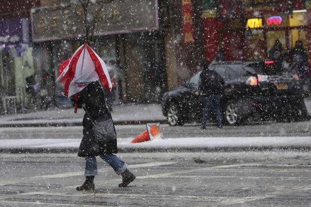 A woman's umbrella collapses in the wind while she crosses the street in New York's Chinatown, Friday, Feb. 8, 2013. Snow began to fall as a massive blizzard headed for the American Northeast on Friday, sending residents scurrying to stock up on food and supplies ahead of a storm poised to dump up to 3 feet of snow from New York City to Boston and beyond. (AP Photo/Mary Altaffer) ORG XMIT: NYMA108