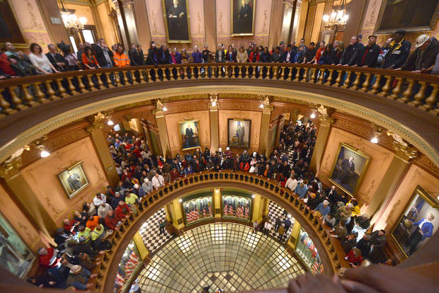 "Pro-union demonstrators crowd the Rotunda to chant Wednesday afternoon Dec. 5, 2012, in the Capitol in Lansing, Mich., after House and Senate Democrats said there was a possibility of ""Right To Work"" legislation coming up for a vote.      (AP Photo/Detroit News,Dale G. Young )  DETROIT FREE PRESS OUT; HUFFINGTON POST OUT"