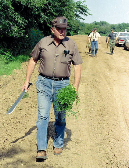 Oklahoma Gov. Henry Bellmon carries several marijuana plants that he cut down using the machete he is holding Thursday Aug. 24, 1989 near Hinton, Oklahoma. Bellmon was on hand to inspect the destruction of more than 180,000 plants by the Oklahoma Highway Patrol and sheriff's deputies. (AP Photo/str-Scott Andersen)