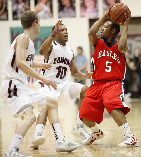 Del City's Deaunte Long (5) tries to pass away from Jordan Woodard (10) and Jordan Thomas (4) of Edmond Memorial during a boys high school basketball game between Edmond Memorial and Del City at Edmond Memorial High School in Edmond, Okla., Friday, Feb. 3, 2012. Photo by Nate Billings, The Oklahoman