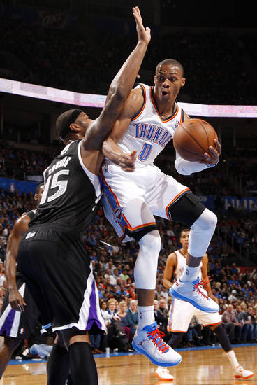 Oklahoma City's Russell Westbrook (0) looks to pass around Sacramento's DeMarcus Cousins (15)  during an NBA basketball game between the Oklahoma City Thunder and the Sacramento Kings at Chesapeake Energy Arena in Oklahoma City, Friday, Dec. 14, 2012. Photo by Bryan Terry, The Oklahoman