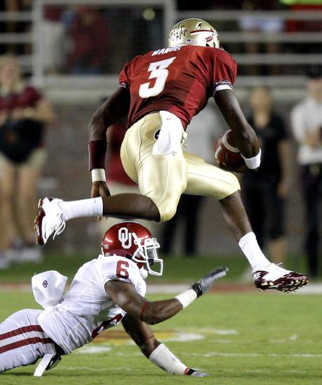 Florida's EJ Manuel (3) leaps over Oklahoma's Demontre Hurst (6) during a college football game between the University of Oklahoma (OU) and Florida State (FSU) at Doak Campbell Stadium in Tallahassee, Fla., Saturday, Sept. 17, 2011. Photo by Bryan Terry, The Oklahoman