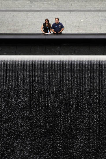 Two people pause before one of the two waterfall pools during a ceremony marking the 10th anniversary of the attacks, at the National September 11 Memorial at the World Trade Center site in Sunday, Sept. 11, 2011, in New York. (AP Photo/Matt Rourke)