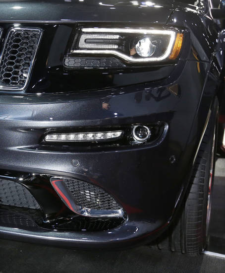 The front lamps on the high-performance SRT version of the 2014 Jeep Grand Cherokee are seen at the North American International Auto Show in Detroit, Tuesday, Jan. 15, 2013. The lamps are tinted black, giving it a distinct look. Ralph Gilles, a Chrysler design leader who also is president and CEO of the SRT brand and motorsports, noted the vehicle has black &quot;kind of like death&quot;, headlamps. (AP Photo/Carlos Osorio) ORG XMIT: MICO123
