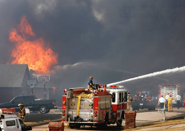 Firefighters battle homes on fire on both sides of Westbury Street in the Oakwood East neighborhood in Midwest City on Thursday.  Photo by JIM BECKEL, THE OKLAHOMAN