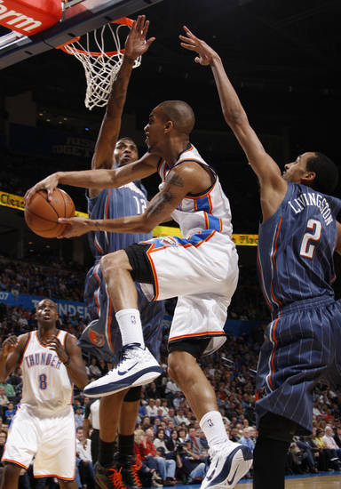 Oklahoma City's Eric Maynor (6) goes between Charlotte's Tyrus Thomas (12) and Shaun Livingston (2) during an NBA basketball game between the Oklahoma City Thunder and the Charlotte Bobcats at the Oklahoma City Arena, Friday, March 18, 2011. Photo by Bryan Terry, The Oklahoman