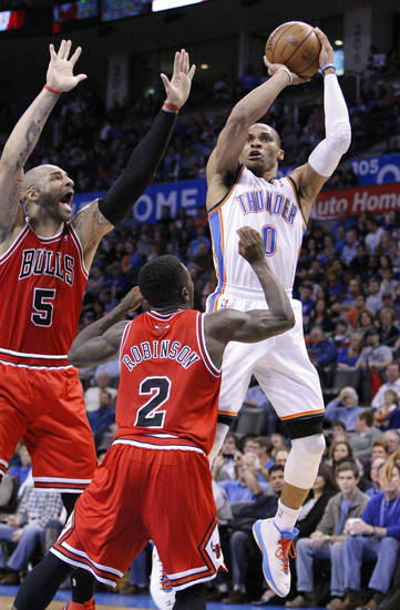 Oklahoma City Thunder guard Russell Westbrook (0) shoots in front of Chicago Bulls Nate Robinson (2) and Carlos Boozer (5) during the third quarter of a NBA basketball game in Oklahoma City, Sunday, Feb. 24, 2013.  Oklahoma City won 102-72.  (AP Photo/Alonzo Adams)