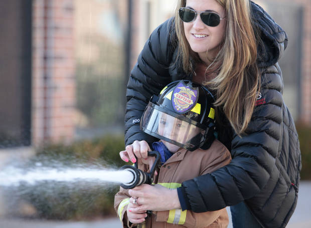 Pierson McIntire gets some help from his mother, Kristy, with spraying a fire hose during Edmond Fire Department's Children's Safety Challenge over spring break. PHOTO BY DAVID MCDANIEL, THE OKLAHOMAN. <strong>David McDaniel - THE OKLAHOMAN</strong>
