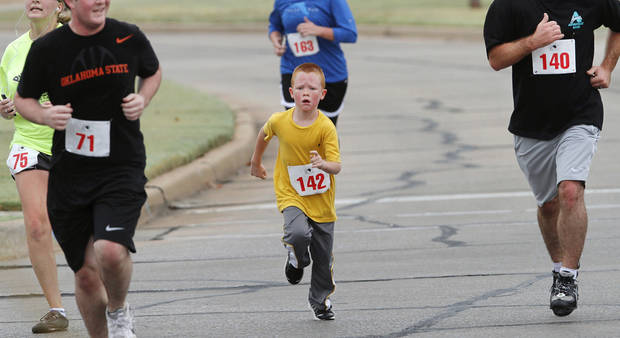 Brandon Lamar, of Yukon, runs alongside adults Satuday on the Renaissance Run course. The 5k run and walk began  at the Midwest City Community Center. Following the race, runners were invited to enjoy a pancake breakfast  at Midwest Regional Medical Center.  Photo by Jim Beckel, The Oklahoman. <strong>Jim Beckel</strong>