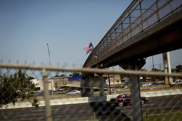 Standing on a pedestrian bridge, Ted Krey, of Yukon, holds an American Flag over I-240 on Wednesday, Aug. 24, 2011. Krey says he will hold the flag over traffic from a different pedestrian bridge around Oklahoma City everyday until Sept. 11. Photo by John Clanton, The Oklahoman