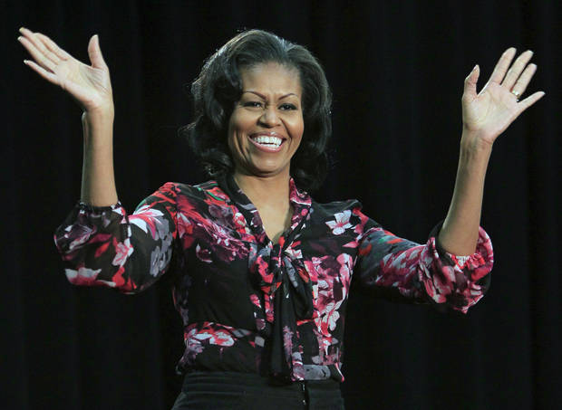 First Lady Michelle Obama acknowledges the crowd as she walks onstage, Saturday, Nov. 3, 2012, during a campaign rally at Miami (Ohio) Unversity in Oxford, Ohio. The First Lady spoke about what's at stake in this election and asked people to help get out the vote. (AP Photo/Al Behrman)