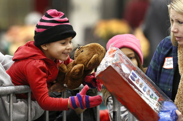 A boy reacts with delight as he accepts a toy from volunteer Angela Owen. Hundreds were served a traditional Christmas meal at the annual Red Andrews Dinner inside the Cox Convention Center on Christmas Day, Dec. 25, 2012. An army of  volunteers showed up despite  snow and ice and hazardous driving conditions. They accompanied each guest through the serving line and carried their trays and seated them at their tables. Other volunteers distributed a small mountain of toys and stuffed animals that were donated for the event.   Photo by Jim Beckel, The Oklahoman