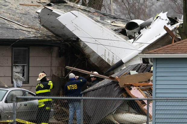 A National Transportation Safety Board investigator and South Bend firefighters early Monday, March 18, 2013, survey the scene of Sunday's fatal plane crash, along Iowa Street in South Bend, Ind. Photo by James Brosher, South Bend Tribune/AP <strong>James Brosher - AP</strong>