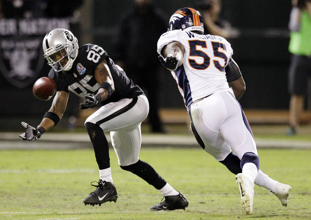 Oakland Raiders wide receiver Darrius Heyward-Bey (85) catches a pass as Denver Broncos linebacker D.J. Williams (55) watches during the second quarter of an NFL football game in Oakland, Calif., Thursday, Dec. 6, 2012. (AP Photo/Ben Margot)
