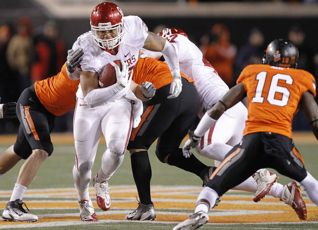 Oklahoma&#039;s Trey Millard (33) runs through the Oklahoma State defense during the Bedlam college football game between the Oklahoma State University Cowboys (OSU) and the University of Oklahoma Sooners (OU) at Boone Pickens Stadium in Stillwater, Okla., Saturday, Dec. 3, 2011. Photo by Chris Landsberger, The Oklahoman
