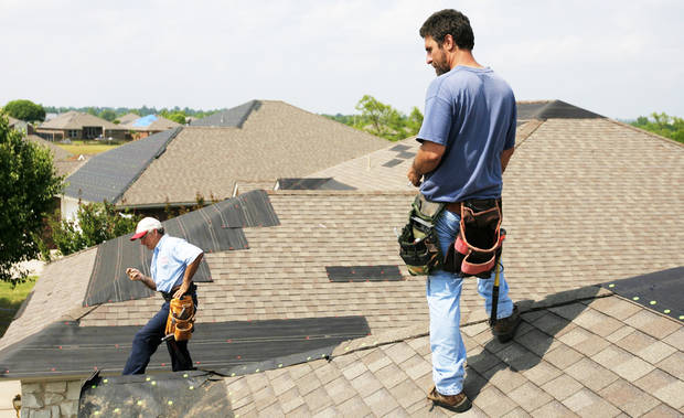 Jim Beres, left, and Allen Vollmer, right, of Good Guys Construction, working with Aegis Roofing, on Tuesday look at temporary roof repairs done at a home in Moore.