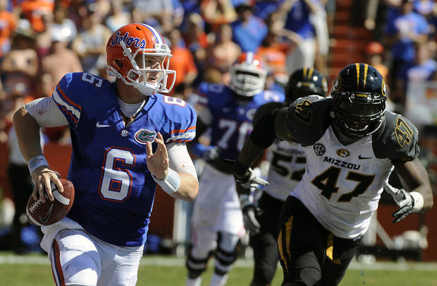 Florida quarterback Jeff Driskel (6) scrambles with the ball as Missouri defensive lineman Kony Ealy (47) tries to stop him during the first half of an NCAA college football game, Saturday, Nov. 3, 2012, in Gainesville, Fla. (AP Photo/Phil Sandlin)