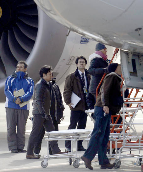 U.S. officials inspect a All Nippon Airways jet which made an emergency landing Wednesday, at Takamatsu airport in Takamatsu, western Japan, Friday, Jan. 18, 2013. An official with Japan&acirc;s transport safety board says four U.S. officials, including two Boeing Co. representatives, have arrived at the airport in western Japan to inspect the troubled Boeing 787 jet. (AP Photo/Kyodo News)  JAPAN OUT, MANDATORY CREDIT, NO LICENSING IN CHINA, HONG KONG, JAPAN, SOUTH KOREA AND FRANCE