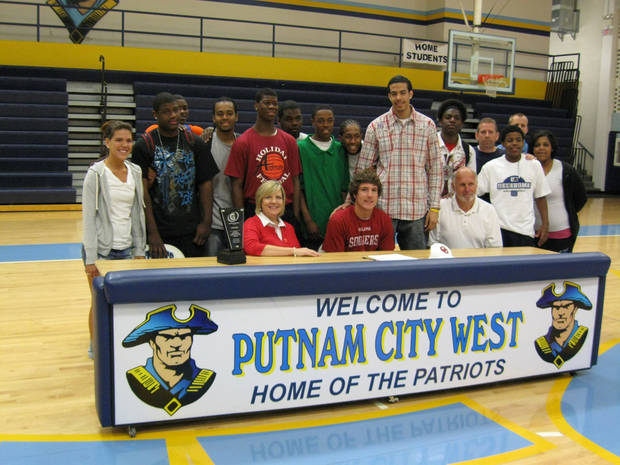 Putnam City West basketball standout Tyler Neal, seated center, poses with his parents and teammates after signing a letter of intent Friday to play basketball at Oklahoma.