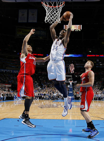 Oklahoma City's Hasheem Thabeet (34) goes up for a dunk between the Clippers Ryan Hollins (15) and Blake Griffin (32) during an NBA basketball game between the Oklahoma City Thunder and the Los Angeles Clippers at Chesapeake Energy Arena in Oklahoma City, Wednesday, Nov. 21, 2012. Photo by Bryan Terry, The Oklahoman