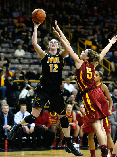 Iowa  center Morgan Johnson (12) puts up a shot against Iowa State  forward Hallie Christofferson (5) during the first half an NCAA college basketball game Thursday, Dec. 6, 2012 at Carver-Hawkeye Arena in Iowa City, Iowa.  (AP Photo/The Gazette,Brian Ray)