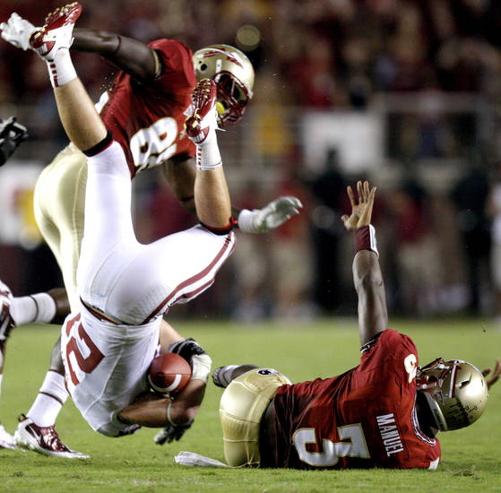 Oklahoma's Tom Wort (21) is flipped beside Florida's EJ Manuel (3) after an interception during a college football game between the University of Oklahoma (OU) and Florida State (FSU) at Doak Campbell Stadium in Tallahassee, Fla., Saturday, Sept. 17, 2011. Photo by Bryan Terry, The Oklahoman