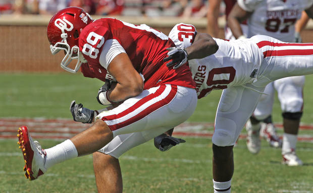 Austin Haywood (89) holds on to a pass defended by Javon Harris (30) during the University of Oklahoma Sooner's (OU) Spring Football game at Gaylord Family-Oklahoma Memorial Stadium on Saturday, April 16, 2011, in Norman, Okla.  