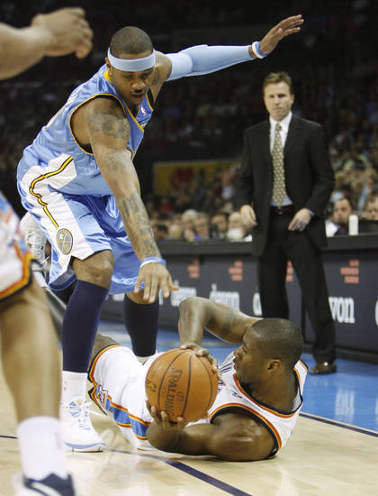 Desmond Mason tries to keep the ball in play in front of Carmelo Anthony in the first half as the Oklahoma City Thunder play the Denver Nuggets at the Ford Center in Oklahoma City, Okla. on Friday, January 2, 2009.  Photo by Steve Sisney/The Oklahoman