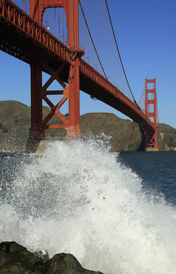 A wave breaks under the Golden Gate Bridge at high tide Thursday, Dec. 13, 2012 in San Francisco. The National Weather Service says so-called King Tides � caused by a rather unique combination of how the sun, the moon and the earth align � will bring the highest tides of the year on Thursday, Friday and Saturday mornings. Along with the high tides, forecasters say a building swell will bring large breaking waves to area beaches. The San Francisco Chronicle reports the combination of high tides and surf has flooded some parking lots in San Francisco and in Marin County. (AP Photo/Ben Margot)