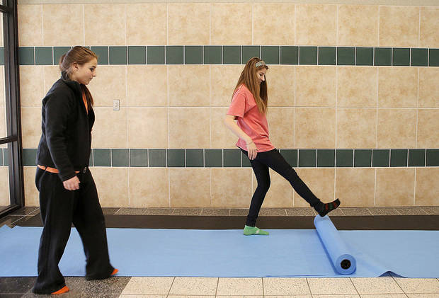 Edmond Santa Fe senior Ashley Neese, 17, at right, and junior Jourdan Sturges, 16, unroll paper to cover the walls of Edmond Santa Fe High School for Double Wolf Dare Week in Edmond, Okla., Friday, Feb. 22, 2013. Photo by Bryan Terry, The Oklahoman