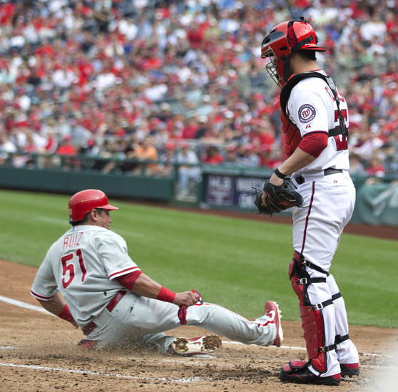 Philadelphia Phillies Carlos Ruiz (51) slides home to score on Darin Ruf's sacrifice fly as Washington Nationals catcher Jesus Flores (26) watches during the fourth inning of a baseball game in Washington, Wednesday, Oct. 3, 2012. The Nationals won 5-1. (AP Photo/Manuel Balce Ceneta)
